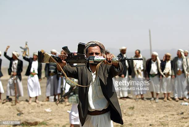 An armed Yemeni man loyal to the Shiite Huthi movement holds up his gun during a tribal gathering against alQaeda militants in the Bani alHarith area...
