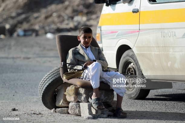 An armed Yemeni Shiite Huthi rebel child mans a checkpoint erected in the capital Sanaa on September 23, 2014. Yemeni President Abdrabuh Mansur Hadi...