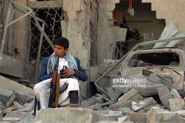 An armed Yemeni youth, loyal to the Shiite Muslim Huthi movement that controls Sanaa, sits amid the rubble on December 5 guarding the damaged house...