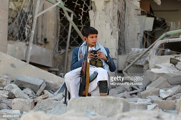 An armed Yemeni youth loyal to the Shiite Muslim Huthi movement that controls Sanaa sits amid the rubble on December 5 guarding the damaged house of...