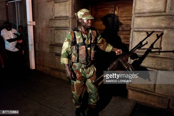 An armed Zimbabwean soldier patrols in the street of Harare as the population celebrates after the resignation of President Mugabe on November 21...