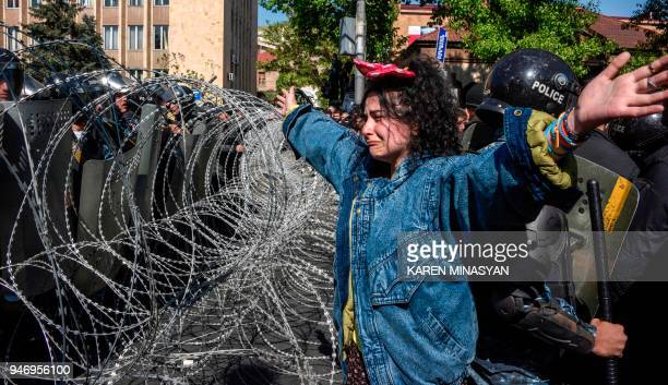 An Armenian opposition supporter gestures in front of barbed wire and police officers standing guard behind their shields during a dispersal of a...