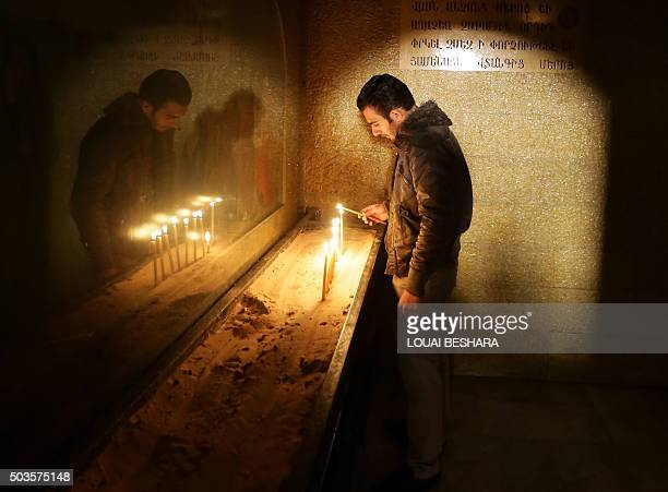 An Armenian Orthodox man lights a candle at the Syrian Saint Sarkis Church during Christmas celebrations on January 6 2016 in Damascus While...