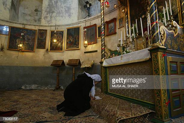 An Armenian Orthodox woman prays at an alter in the Church of the Nativity at the start of the Armenian Christmas Eve celebrations 18 January 2007 in...
