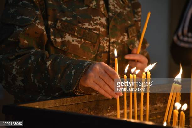 An Armenian person lights candles in a church in Yerevan on October 17 for Armenians killed during fighting over the breakaway region of...