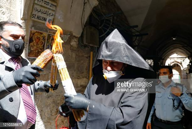 An Armenian priest wearing a protective mask and gloves passes on the Holy Fire lit in the church of the Holy Sepulchre as very few Orthodox...
