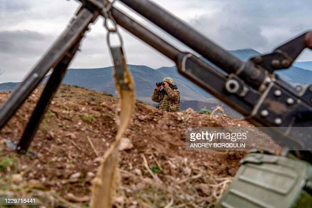 An Armenian soldier looks through binoculars during a patrol at the check point nearby a demarcation line outside Askeran on November 21 as...