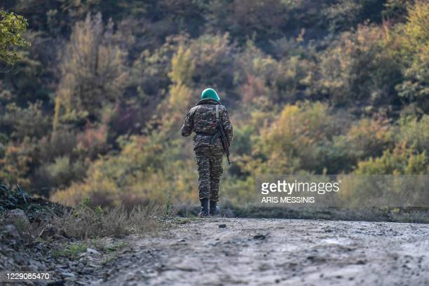 An Armenian soldier walks along a road during the ongoing fighting between Armenia and Azerbaijan over the disputed region on October 15, 2020. - The...