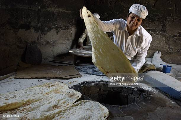 An Armenian woman makes traditional unleavened flat bread lavash during a lavash festival in the village of Pokr Vedi south of Yerevan near the...