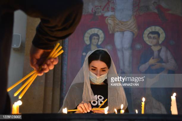An Armenian woman, wearing a face mask, prays in a church in Yerevan on October 17 for Armenians killed during fighting over the breakaway region of...