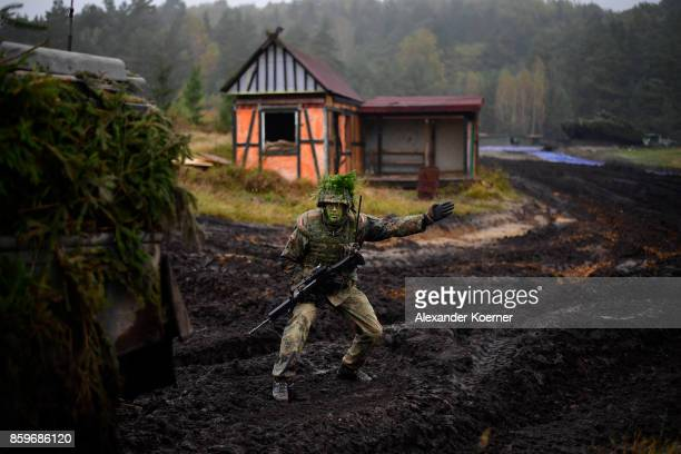 An armored infantryman of the Bundeswehr the German armed forces acts during a simulated attack during military exercises on October 10 2017 near...