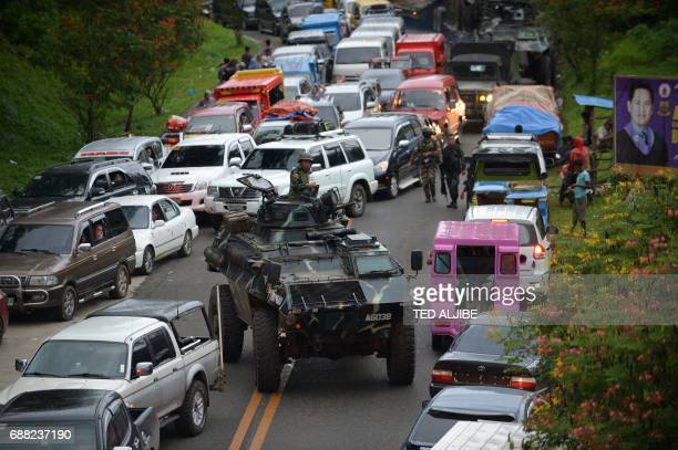 An armored personnel carrier moves amongst stuck vehicles of residents fleeing Marawi, in the southern island of Mindanao on May 25 as fighting rages...