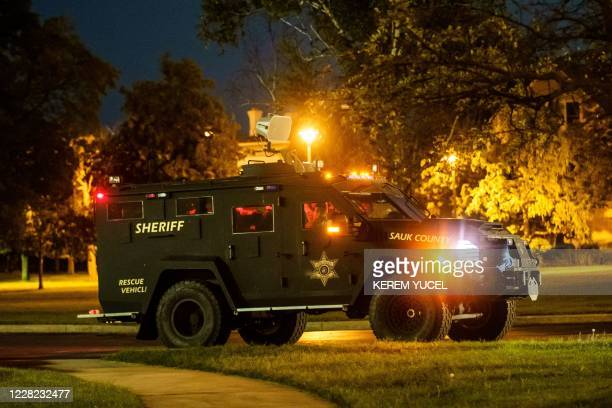 An armored Sheriff's vehicle is waiting in the street to prevent the protesters from breaking curfew on August 27, 2020 in Kenosha, Wisconsin. - A...