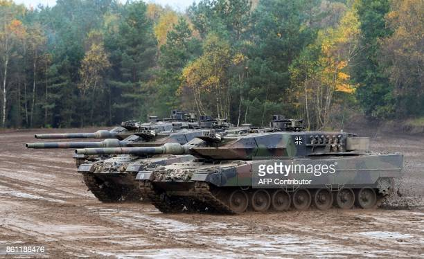 An armored unit with Leopard 2 A7 main battle tanks of the German armed forces Bundeswehr drives through the mud in the context of an informative...