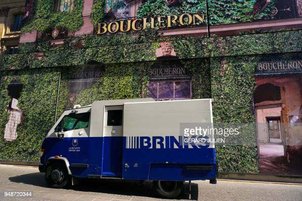 An armored van of the Brink's security company drives past a giant advertising tarpaulin on the facade of French jewellery Boucheron on the Place...