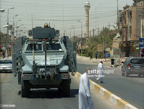An armored vehicle carries officers of the US Army Corps of Engineers as they inspect reconstruction projects in Fallujah Iraq on July 23 2010 The...