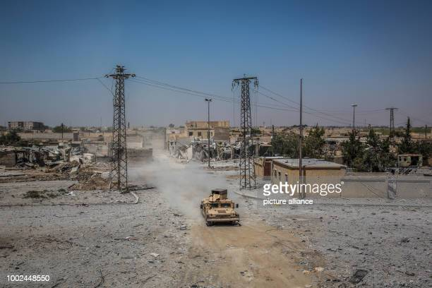 An armored vehicle of the Syrian Democratic Forces drives along the front line in the Al Dariya neighborhood in western Raqqa, Syria, 24 July 2017. A...