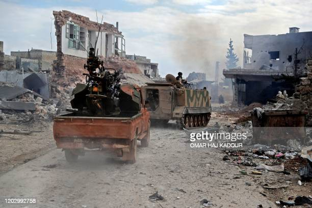 """An armoured personnel carrier carrying members of the """"Syrian National Army"""", an alliance of Turkey-backed rebel groups, followed by a pickup truck..."""