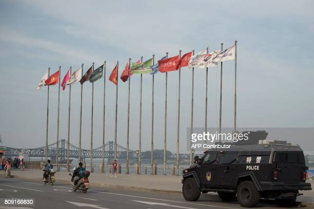 An armoured police van is seen next to the Friendship bridge on the Yalu River connecting the North Korean town of Sinuiju and Dandong in Chinese...