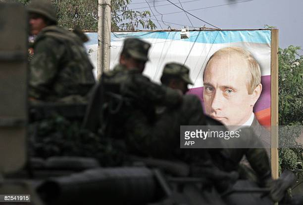 An armoured troopcarrier with Russian soldiers on the top passes a banner featuring a portrait of Russian Prime minister Vladimir Putin as they leave...
