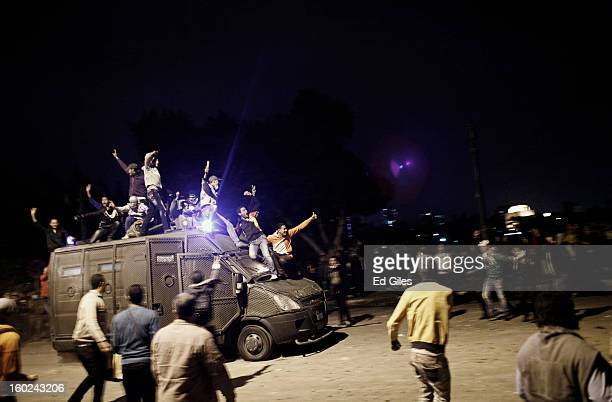 An armoured vehicle belonging to the Egyptian riot police or Central Security Forces is driven along a road with Egyptian protesters on top after...