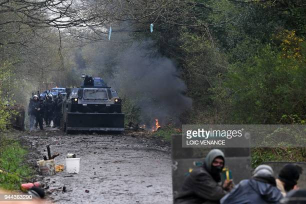 An armoured vehicle of riot Gendarmes makes its way through the woods towards protesters and barricades as clashes erupt during a police operation to...