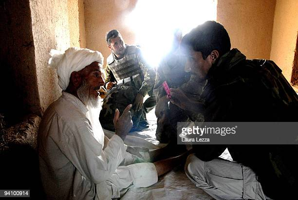 An army doctor of the Folgore Parachute Brigade visit an elder of a village with the help of the interpreter in a small and remote village on...