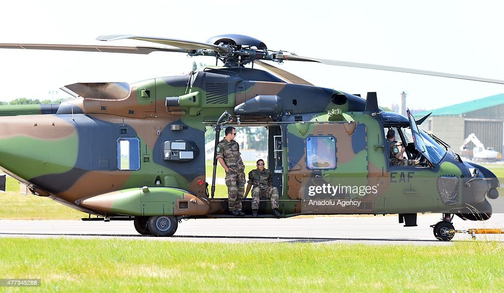 An army helicopter prepares for an aerial display as crew members sit during the 51st international Paris Air Show at Le Bourget, near Paris, France on June 16, 2015.