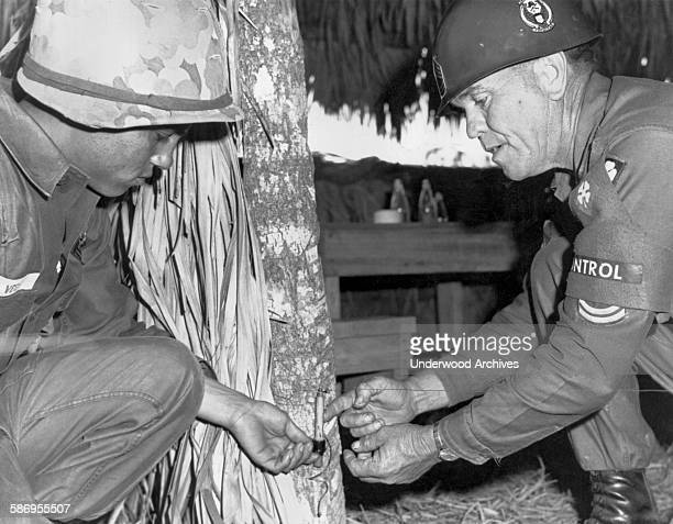 An Army instructor shows a recruit how to deactivate a trip wire used by the Viet Cong in Vietnam 1967