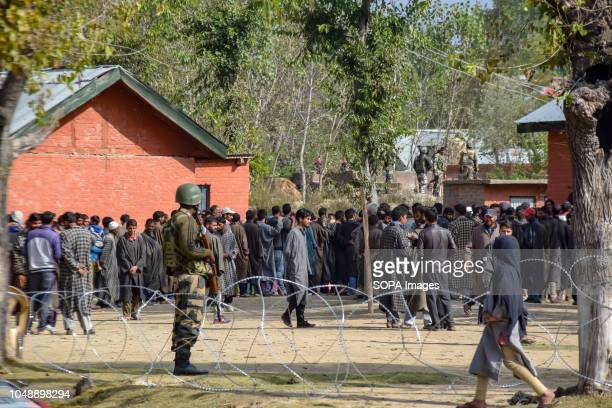SUMBAL BARAMULLA JAMMU KASHMIR INDIA An army man seen looking on as Kashmiri voters wait in a queue outside the polling station during elections at...