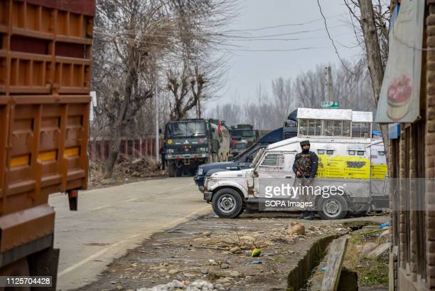An army man seen standing on guard in front of an armoured vehicle during gun fight at Pinglena village. Three militants, four Indian army men, a...