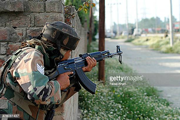 CONTENT] An Army man stands alert near shootout scene in Hyderpora SrinagarKashmir where militants kill five Indian army men and injure several others