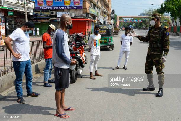 An Army member passing on corona virus related information to residents during the covid 19 pandemic. Bangladesh has confirmed 11617 cases, 1403...