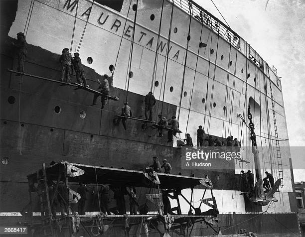 An army of workmen suspended by travelling cradles give a coat of white paint to the hull of the great Cunard liner Mauretania in its berth at...