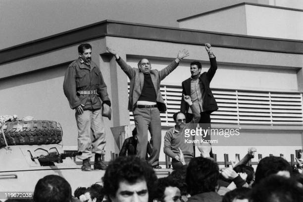 An army officer guarding the SAVAK headquarters in Tehran stands on top of an armoured personnel carrier with three demonstrators as a gesture of...