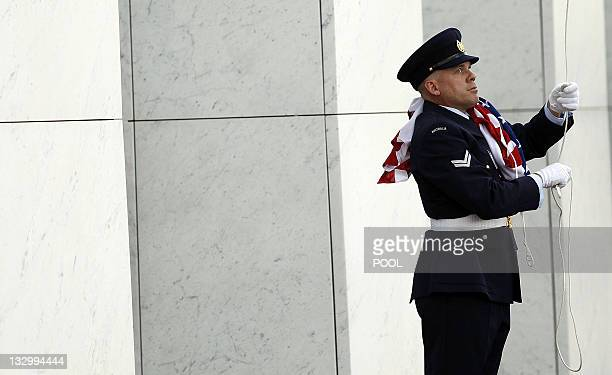 An Army officer packs up flags after US President Barack Obama attended a welcoming ceremony on the forecourt of Parliament House in Canberra on...