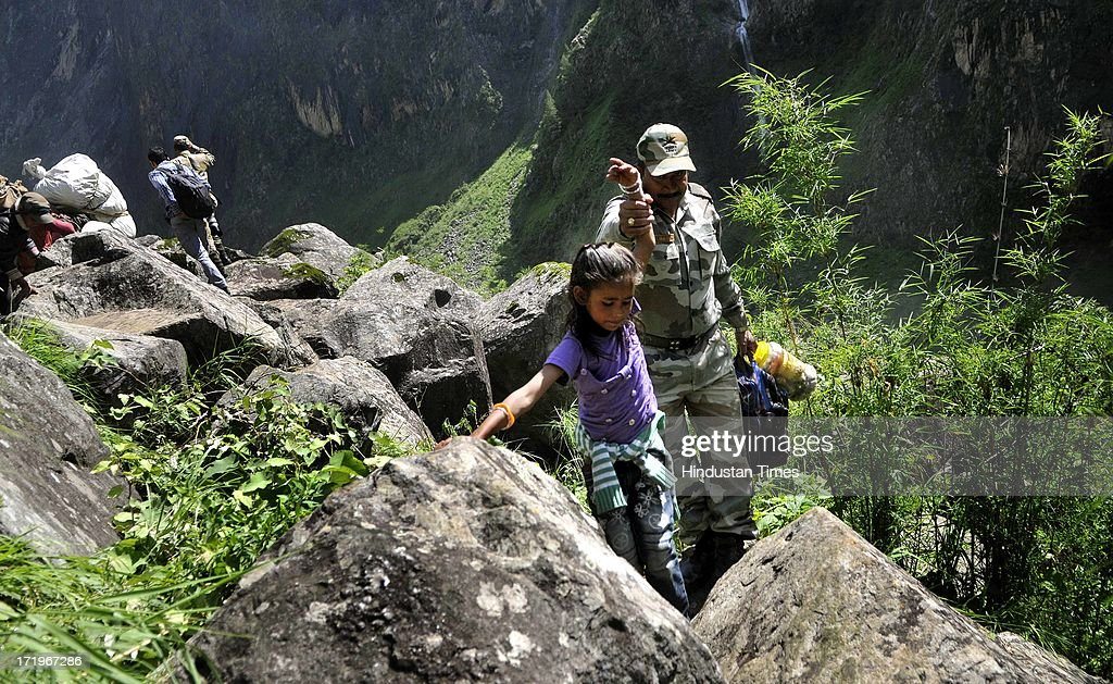 An Army personnel helping a little girl to cross a rocky stretch at Govind Ghat on June 30 2013 in Uttarakhand, India. People who are stranded at Badrinath got agitated as their token for helicopter rescue are being mismanaged and henceforth opted to walk down through mountains.