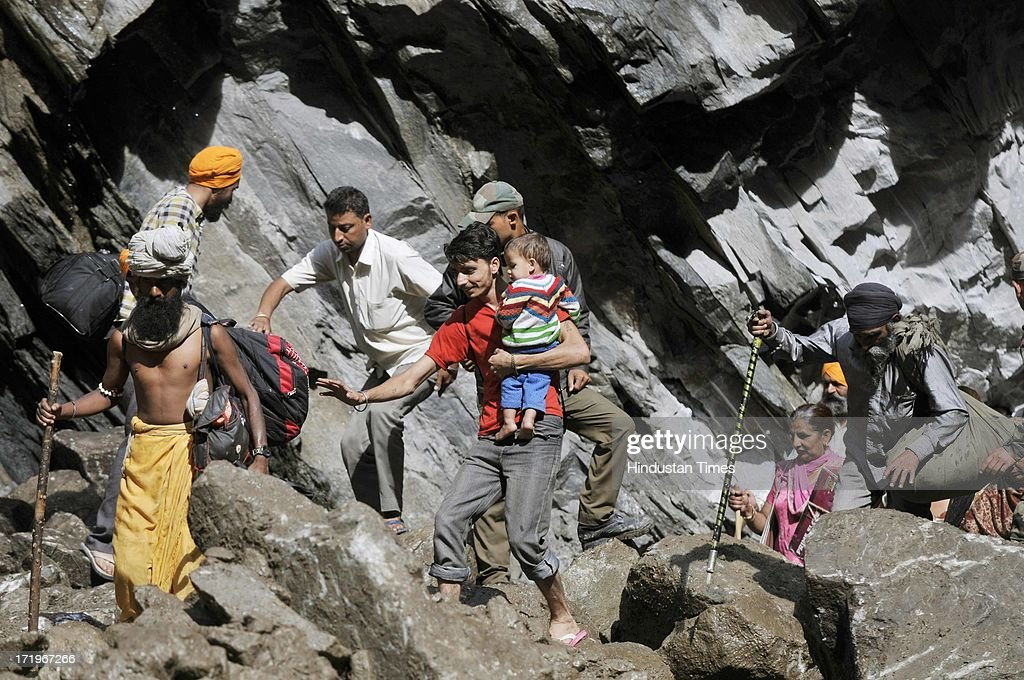 An Army personnel helping people to cross a rocky stretch at Govind Ghat on June 30 2013 in Uttarakhand, India. People who are stranded at Badrinath got agitated as their token for helicopter rescue are being mismanaged and henceforth opted to walk down through mountains.