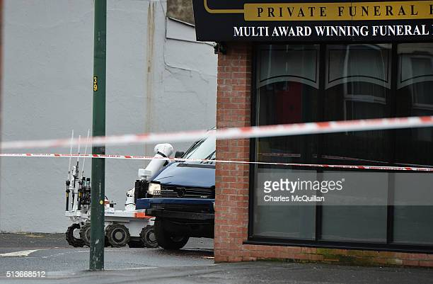 An army remote controlled robot inspects the damaged van following a suspected car bomb attack on a prison officer at Hillsborough Drive on March 4...