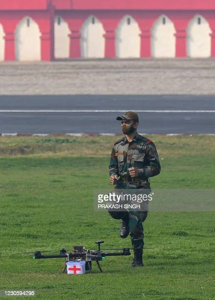 An army soldier collects the first-aid box off a drone from the offensive swarm drone system as they demonstrate skills during a ceremony to...