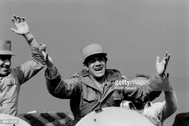 An army soldier guarding the SAVAK headquarters in Tehran comes out of an armored personnel carrier waving to the crowd as a gesture of unity on the...
