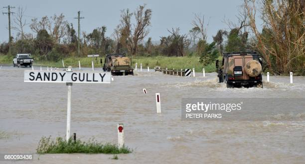 An army vehicle drives through floodwaters near the Queensland town of Bowen on March 29 after the area was hit by Cyclone Debbie Towns remained cut...