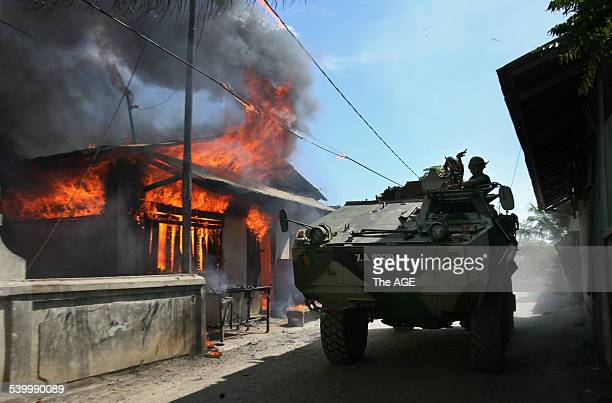 An army vehicle rolls past a house that has been torched in the Komoro district of the East Timorese capital Dili Street fighting has broken out and...