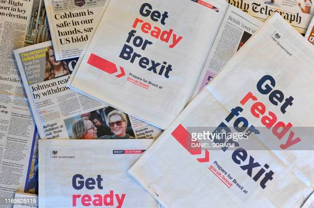 An arrangement of newspapers photographed as an illustration in London on September 2 shows a fullpage advertisement taken out by the UK Government...