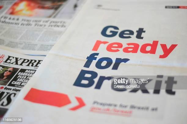 An arrangement of newspapers photographed as an illustration in London on September 2 shows a full-page advertisement taken out by the UK Government...