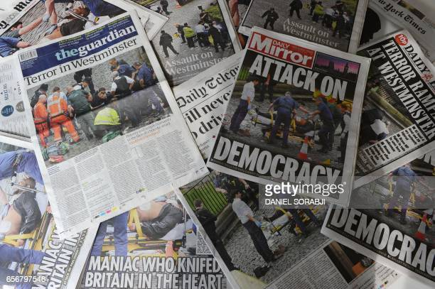 TOPSHOT An arrangement of newspapers pictured in London on March 23 as an illustration shows the front pages of the UK daily newspapers reporting on...