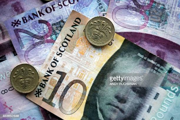 An arrangement of Scottish pound sterling banknotes and pound coins showing the thistle of Scotland are spread on a table top on August 19 2014 in...