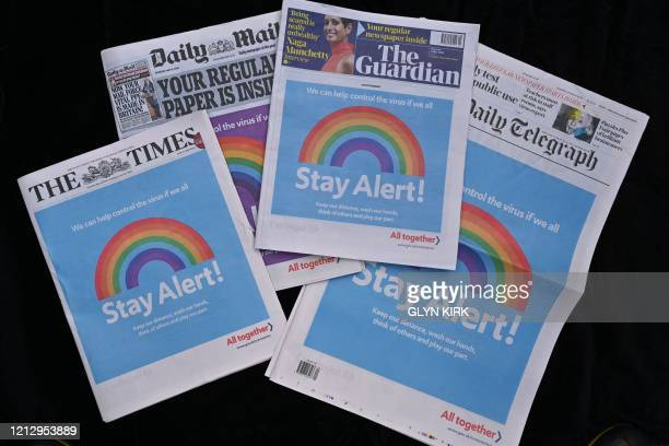 An arrangement of UK daily newspapers photographed as an illustration in London on May 14 shows a front page advertisement of the government's new...