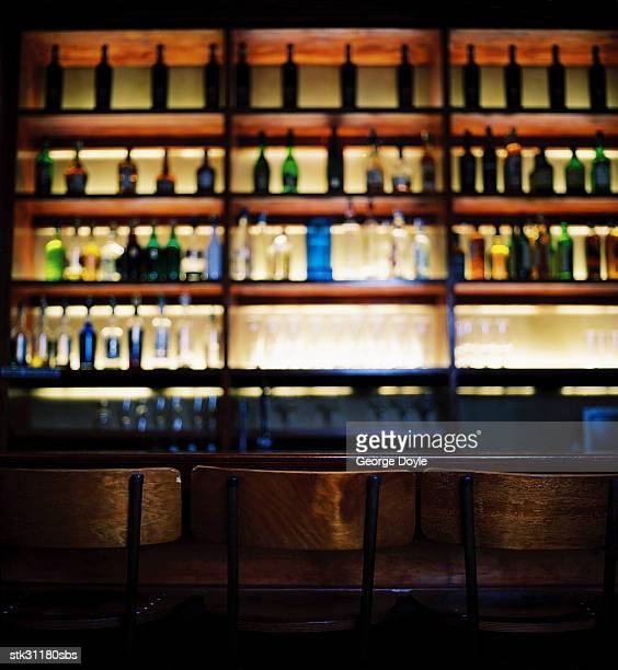 an array of bottles kept in shelves at a bar
