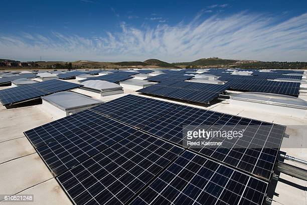 an array of solar panels mounted on the roof of a commercial building help reduce energy costs. - solar energy dish stock pictures, royalty-free photos & images